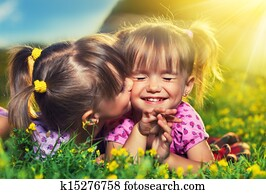 happy family. little girls twin sisters kissing and laughing in the summer outdoors