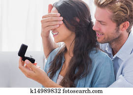 Man hiding his wife's eyes to offer her an engagement ring