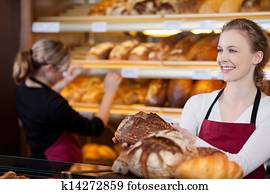 saleswoman in bakery in front of shelves