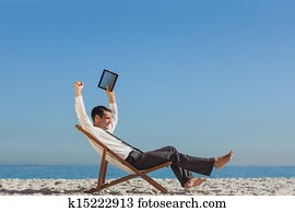 898fc27564 Relaxed man sitting on beach chairs and touching tablet Stock Photo ...