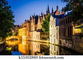 Water canal and medieval houses at night in Bruges