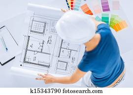 woman with color samples and blueprint