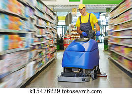 worker cleaning store floor with machine