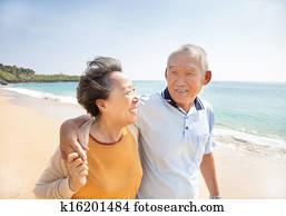 happy asian seniors walking on the beach