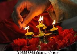 diwali festival of lights , hand lighting an indian oil lamp