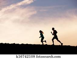 Silhouette of man and woman running jogging together into sunset, Wellness fitness concept