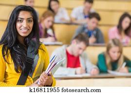 Smiling female with students sitting at the lecture hall