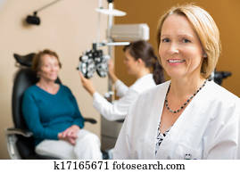 Confident Optometrist With Colleague Examining Patient