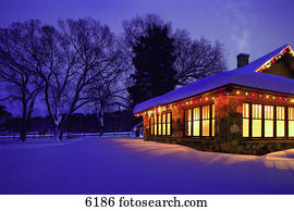 Cottage with Christmas lights in the snow