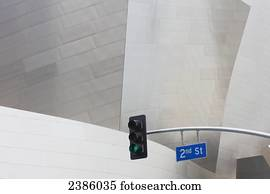 A streetlight and road sign beside a modern building; California, United States of America
