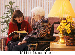 Woman reading to senior relative on wheelchair