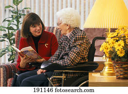 Woman reading to senior relative in wheelchair