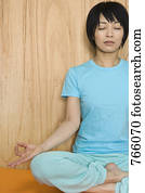 Group Of Young Women Sitting In Lotus Position Meditate