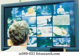 Man looking at televisions