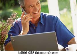 Man using laptop computer and cellphone