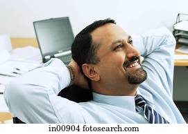 Businessman in office, hands behind head