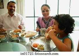Family of three sitting down to a meal