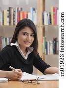 Woman studying in library, looking at camera