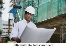 Man with helmet, looking at plans
