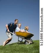 Father Pushing Baby Son In Wheelbarrow Stock Photography