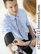 Young man having blood pressure taken