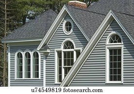 Window with shingled roof in single family home