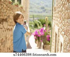 146648cf438 Portrait of boy photographing village street using smartphone