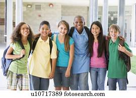 Six students standing outside school together smiling