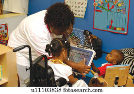 Teacher with two children with multiple disabilities, explaining and demonstrating how to use a communication device.