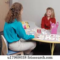 Cute young girl with a disability with her therapist during a speech therapy session.
