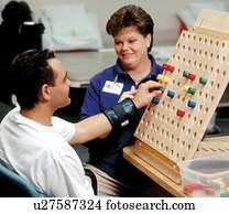 Man with a disability putting pegs in a board during a session with his occupational therapist.